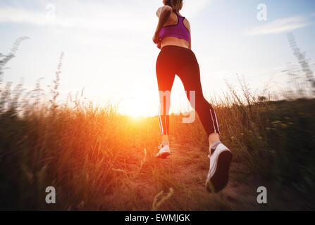 Young woman running on a rural road at sunset in summer field. Lifestyle sports background - Stock Photo