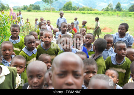 Group of Ugandan school children from a rural school stare at the camera while outside - Stock Photo