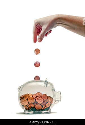 Hand feeding piggy bank..pennies dropping into bank from hand - Stock Photo