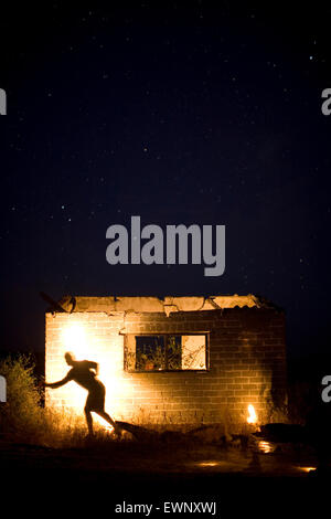 Silhouette of man on a building at night. Baja California, Mexico. - Stock Photo