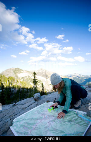 Woman using a map and compass while backpacking in the Montana mountains. - Stock Photo