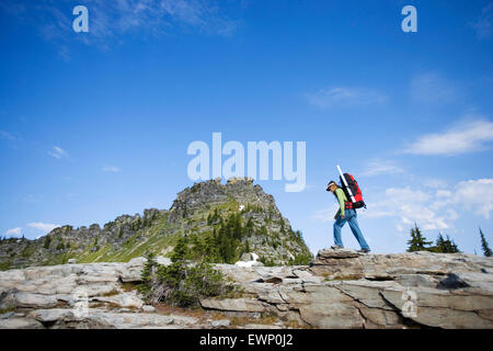 Woman backpacking in a wilderness area under a bright blue sky. - Stock Photo