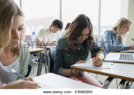 College students taking exam in classroom - Stock Photo