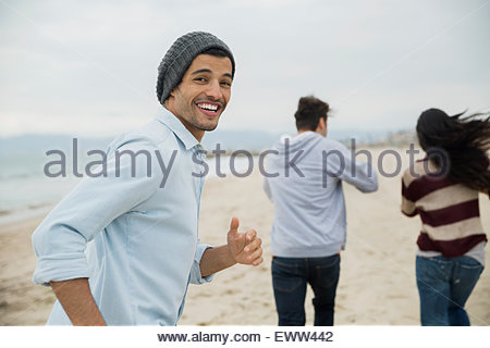 Portrait smiling man running with friends on beach - Stock Photo
