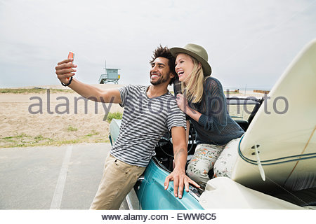Young couple convertible surfboard taking selfie at beach - Stock Photo