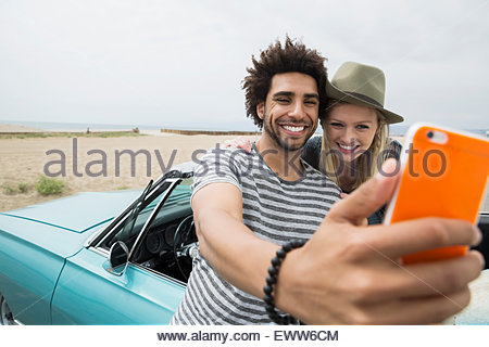 Young couple taking selfie in convertible at beach - Stock Photo