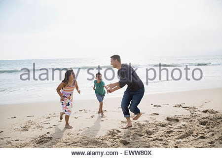 Playful family running on sunny beach - Stock Photo
