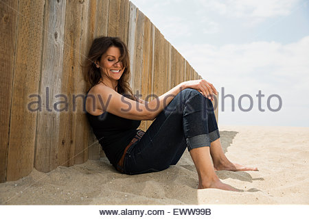 Smiling woman sitting against beach wall - Stock Photo