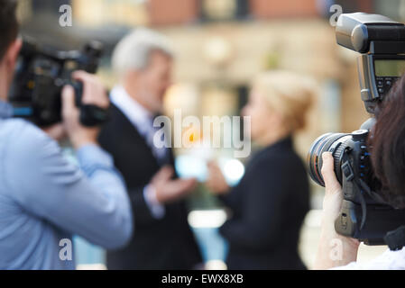 Photographer Taking Pictures Of Female Journalist Interviewing Businessman - Stock Photo