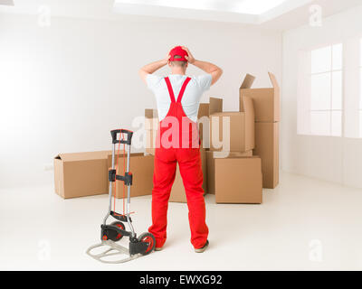 rear view of delivery man facing pile of cardboard boxes, holding his hands on his head, looking worried - Stock Photo