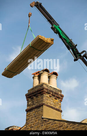 Timber / wood / planks / joist / joists being delivered by crane to a house roof top / new dorma extension. UK - Stock Photo