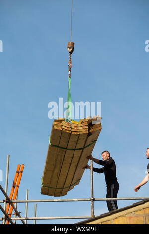 Timber being delivered by crane to a worker builder on scaffolding & Victorian terraced house roof top / new dorma - Stock Photo