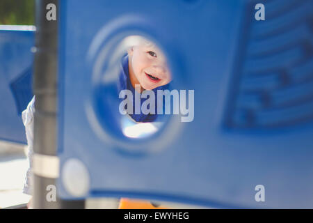 Boy looking through a hole in climbing frame at playground - Stock Photo