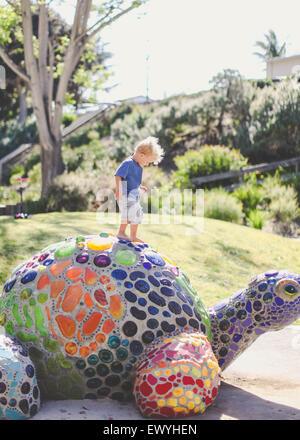 Boy standing on a mosaic turtle, Laguna Beach, Orange County, California, USA - Stock Photo