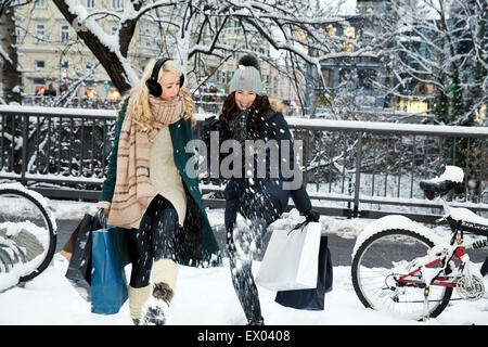Two mid adult women in snow with shopping bags - Stock Photo