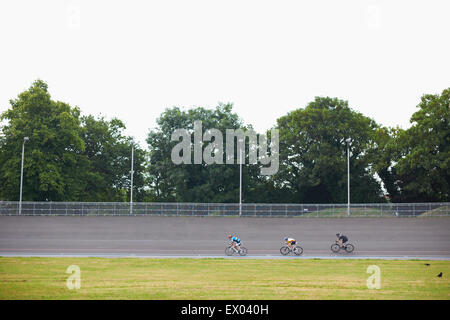 Three cyclists cycling on track at velodrome, outdoors - Stock Photo