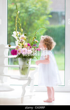 Adorable baby girl with curly hair wearing a white dress smelling beautiful flowers next to a wind and door to the - Stock Photo