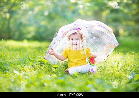 Happy laughing baby girl playing under a colorful umbrella in a warm summer rain - Stock Photo