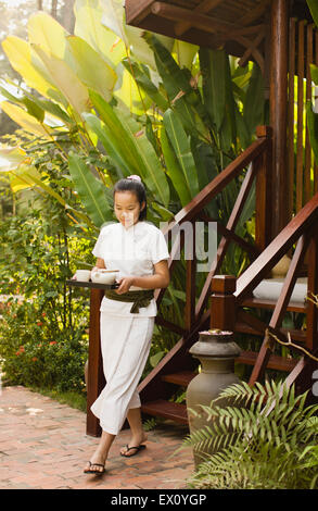 A spa therapist carries tea down the steps from one of four spa treatment rooms at La Residence Phou Vao. Luang - Stock Photo