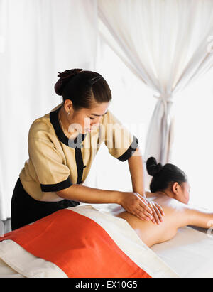 Woman receiving Aroma Thai Massage in spa treatment tents. Angsana Spa at Maison Souvannaphoum. Luang Prabang, Laos. - Stock Photo
