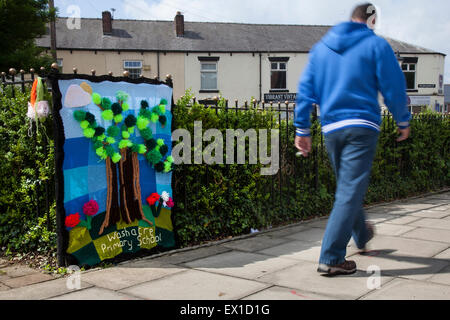 Westhoughton, Lancashire, UK 4th July, 2015.  Cernan Elias ages 42, walks past the Yarn Bomb from 'Washacre Primary - Stock Photo