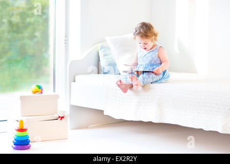 Adorable toddler girl reading a book sitting on a white bed at a big window with garden view - Stock Photo