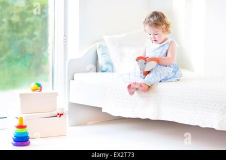 Beautiful curly toddler girl reading a book sitting on a white bed next to a big window with garden view - Stock Photo