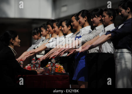 Candidates attend an etiquette test during a job fair recruiting the airline attendants for the 2010 Guangzhou Asian - Stock Photo