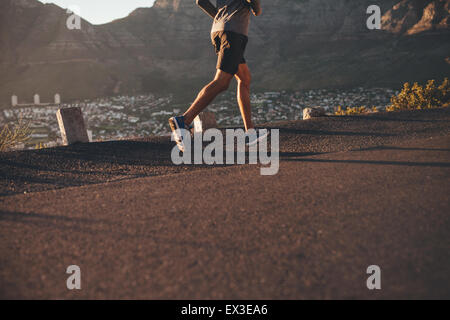 Low section image of young man running on country road in morning. Focus on male athlete legs. - Stock Photo