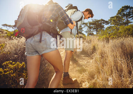 Hiker helping his girlfriend uphill in the countryside. Couple hiking in mountain on a summer day. - Stock Photo