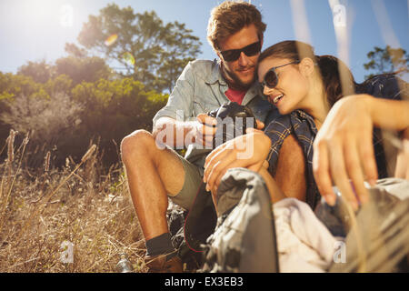 Outdoor shot of hiker couple looking at their camera on a summers day. Caucasian man and woman on hiking trip taking - Stock Photo
