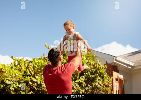 Young man lifting his daughter high in the air. Happy father and daughter playing in their backyard on a sunny day. - Stock Photo