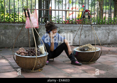 Hanoi Vietnam woman sells chestnuts while talking on her mobile phone just outside the Temple of Literature - Stock Photo