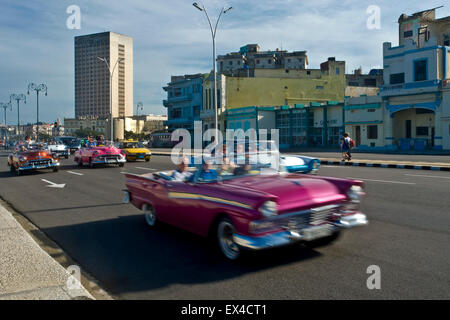 Horizontal view of classic old American cars driving along the Malecon in Havanna, Cuba. - Stock Photo