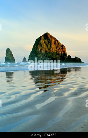 Haystack Rock reflected on water and ripples, Cannon Beach, Oregon USA - Stock Photo