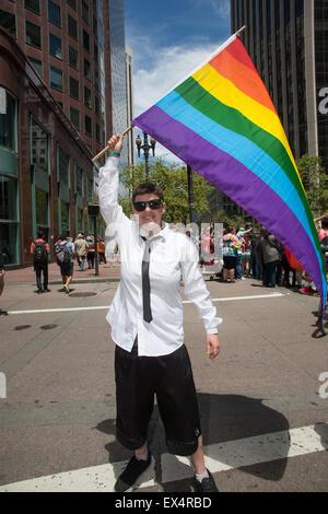 Aly Boyle of San Jose, CA waves a rainbow flag at the San Francisco Pride Parade. - Stock Photo