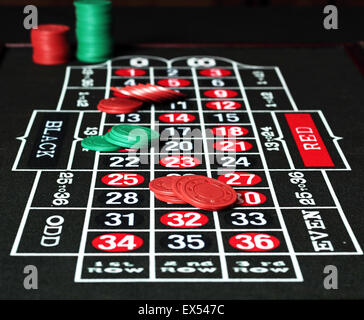 Red and green jetons placed on a roulette table. - Stock Photo
