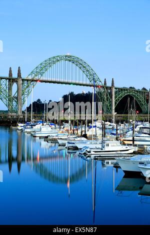 Boats moored in Port of Newport Marina and Yaquina Bay Bridge, Newport, Oregon USA - Stock Photo