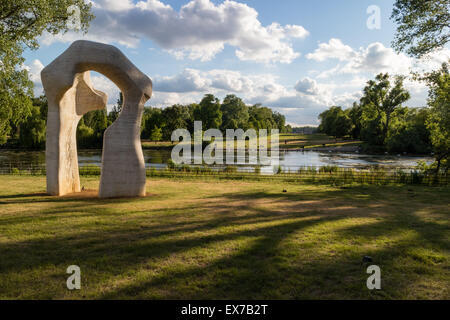 Henry Moore's sculpture The Arch in Kensington Gardens, London, looking across the Long Water towards Kensington - Stock Photo