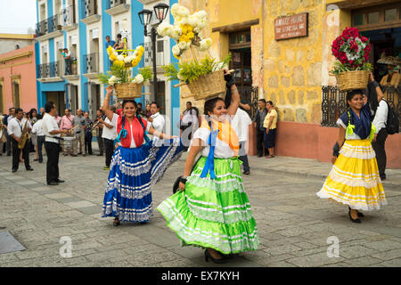 Women in traditional costume dancing and carrying flower baskets on their heads leading a parade at a festival in - Stock Photo