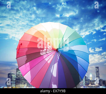 Conceptual picture of a couple kissing behind a colorful umbrella - Stock Photo