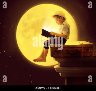 Cute little kid reading a book in the moon light - Stock Photo