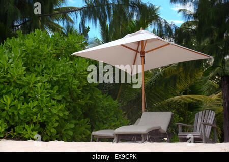 chairs are under the trees on the sandy shores of the Indian Ocean, Denis island, Seychelles - Stock Photo