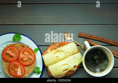 Deli ham and gouda cheese sandwich roll with a cup of hot coffee on top of a wooden table - Stock Photo