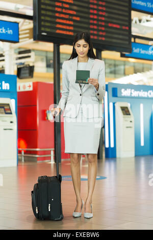 beautiful young businesswoman with luggage standing at airport - Stock Photo