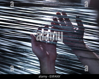 Close up of hands holding carbon fibre on loom in carbon fibre factory - Stock Photo
