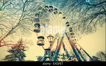Retro old film faded picture of ferris wheel in a park. - Stock Photo