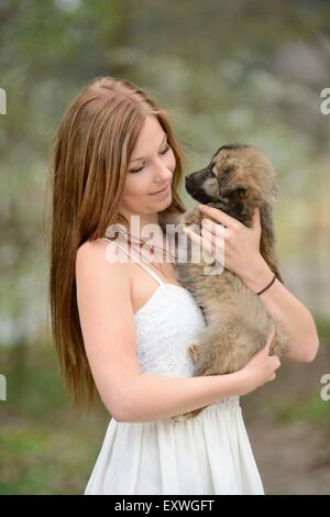 Young woman with a mixed breed dog puppy in garden - Stock Photo