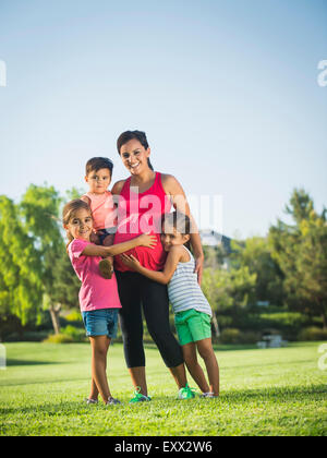 Pregnant mother and children (2-3, 6-7, 8-9) in park - Stock Photo