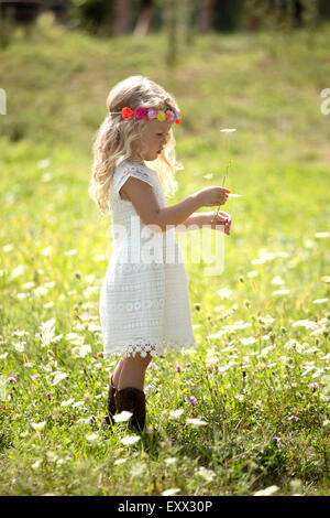 Cute girl (4-5) in white dress standing in meadow - Stock Photo